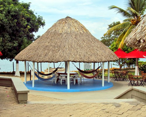 View of dining area covered with thatched sunshade alongside the beach.