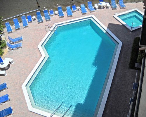 An outdoor swimming pool and hot tub with chaise lounge chairs.