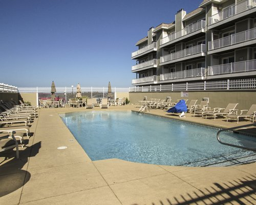 Outdoor swimming pool with chaise lounge chairs and sunshade alongside multiple unit balconies.
