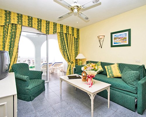 A well furnished bedroom with a television double pull out sofa and patio.