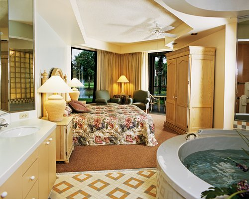 A well furnished bedroom with bathtub and single sink vanity.