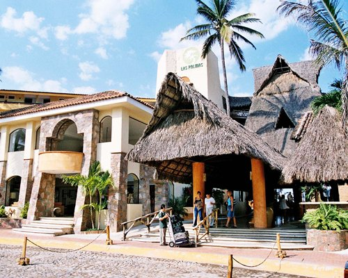 Exterior view and entrance of Hotel Las Palmas Beach Resort with closed thatched sunshade.