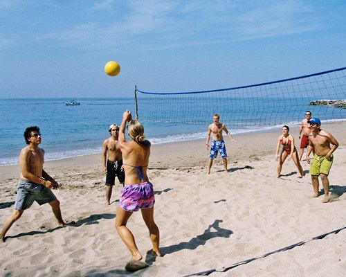 People playing beach volleyball alongside the ocean.