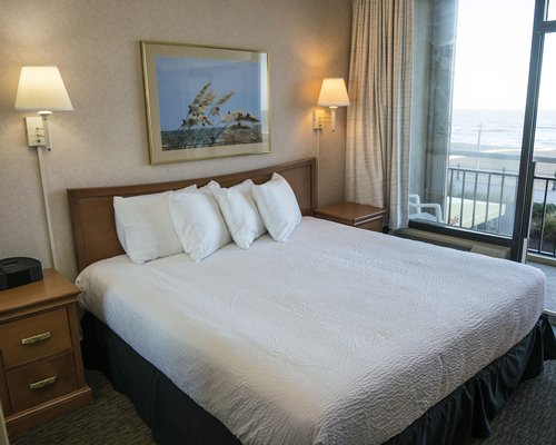 A well furnished bedroom with a queen size bed and ocean view.