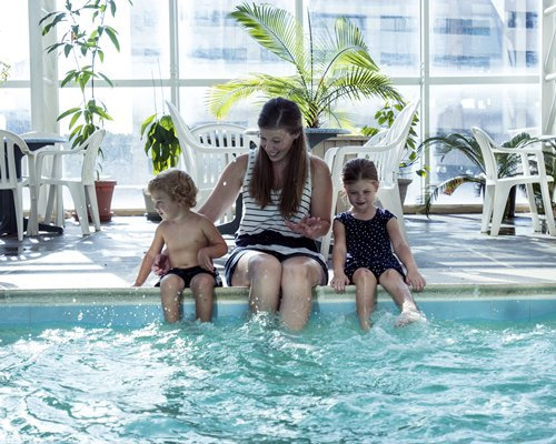 A woman with her kids enjoying alongside the indoor swimming pool.