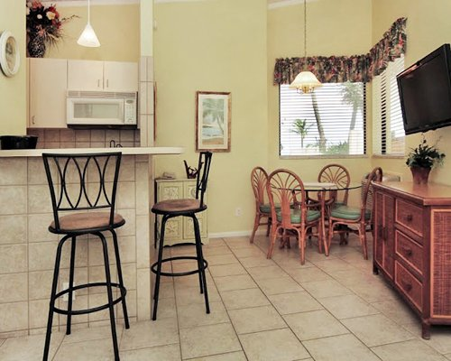 A well equipped kitchen with a breakfast bar television and glass top dining table.