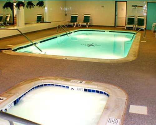 An indoor swimming pool and hot tub with chaise lounge chairs.