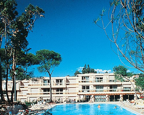 Exterior view of Maeva Clubhotel Saint Raphael with outdoor swimming pool surrounded by landscapin.