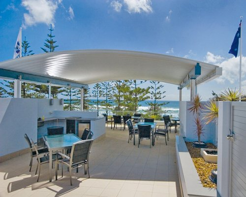 An outdoor glass top dining area alongside the ocean.