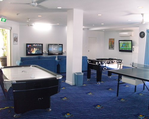 An indoor recreational room with soccer pool and ping pong table.
