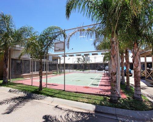 A street view of an outdoor tennis court.