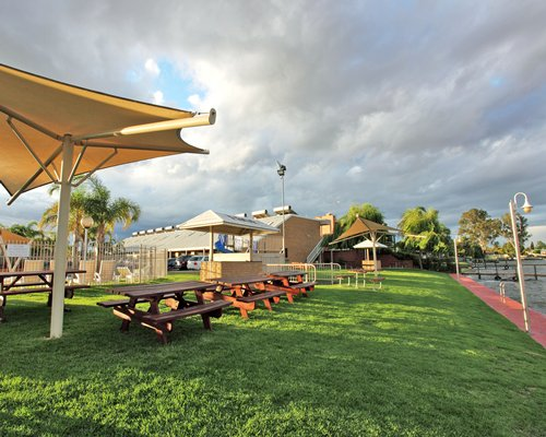 Outdoor picnic area with wooden benches and sunshades.