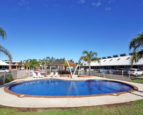 Outdoor swimming pool with chaise lounge chairs and palm trees alongside parking lot.