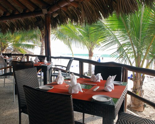 Restaurant with closed thatched sunshade and palm trees alongside the beach.