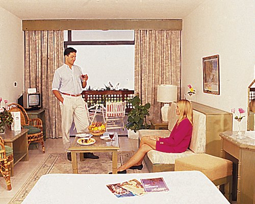 A couple in a well furnished living room with television bed and balcony.