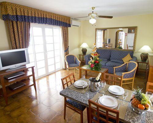 A well furnished living room with the television and dining area.