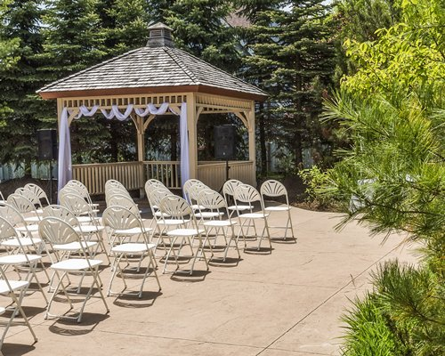 View of wedding set up with patio furniture surrounded by woods.