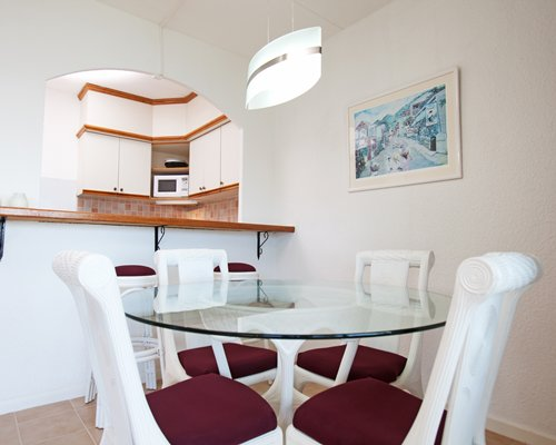 A well furnished glass topped dining table and a kitchen area with breakfast bar.