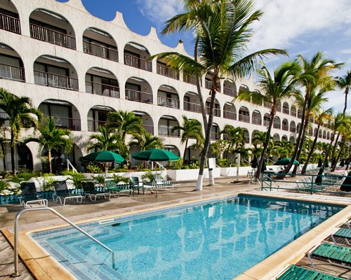 Outdoor swimming pool with chaise lounge chairs sunshades and palm trees alongside multiple balconies.