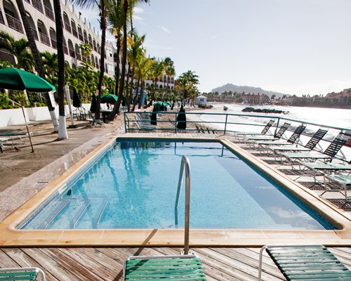 An outdoor swimming pool with chaise lounge chairs sunshades alongside the resort unit.