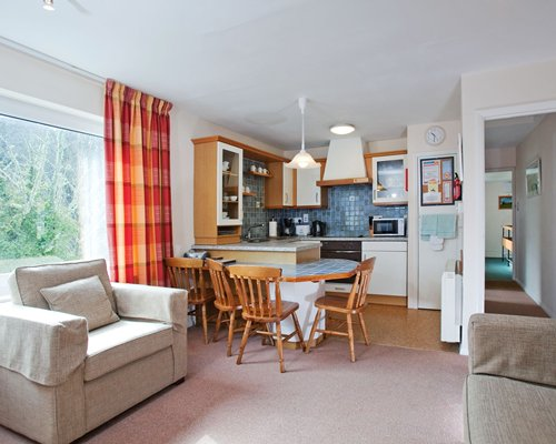 A well furnished living room with open plan kitchen dining area and breakfast bar.