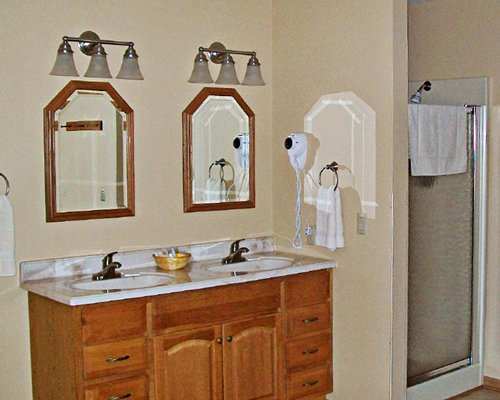 A bathroom with a shower stall and two closed sink vanity.