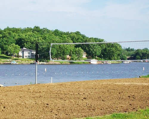 Outdoor recreation area with volleyball net alongside the lake surrounded by wooded area.