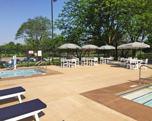 A view of patio furniture with sunshades alongside the swimming pool.