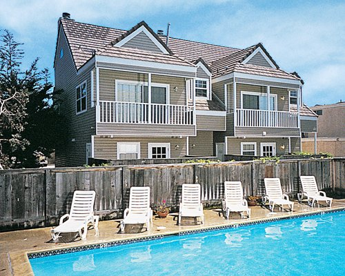Outdoor swimming pool with chaise lounge chairs alongside multiple unit balconies.