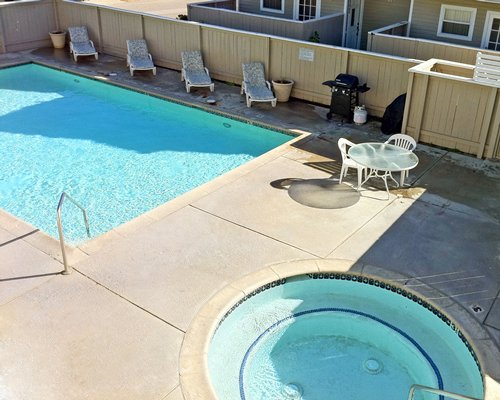 An outdoor swimming pool and hot tub with chaise lounge chairs and patio furniture.