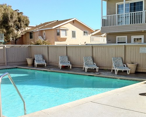 Outdoor swimming pool with chaise lounge chairs alongside multiple units.
