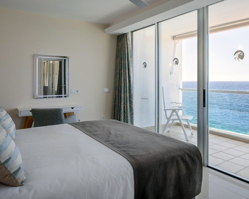 A well furnished bedroom alongside a balcony with an ocean view.