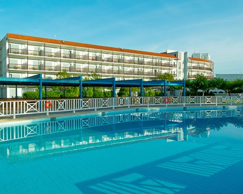 A large outdoor swimming pool with trees alongside multi story resort units.