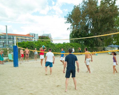 View of people playing volleyball alongside multi story resort units.