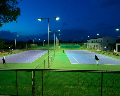View of two outdoor tennis courts at night.