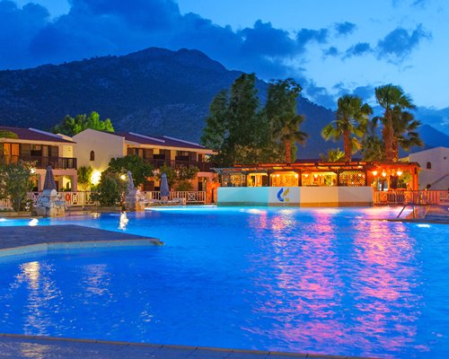 An outdoor swimming pool alongside multiple units at night.