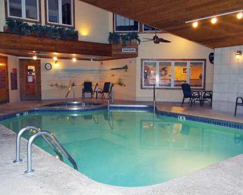 Indoor swimming pool with hot tub and patio chairs.