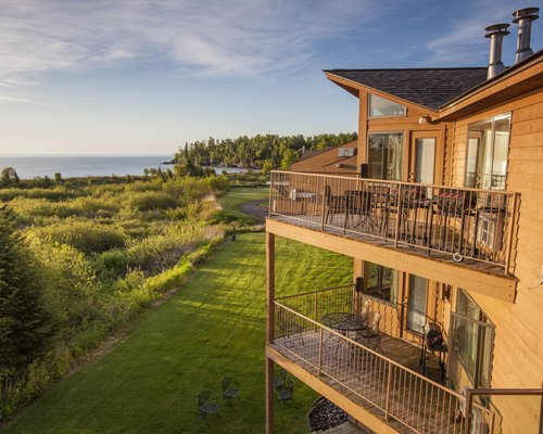 Exterior view of a unit with balconies surrounded by wooded area alongside the ocean.