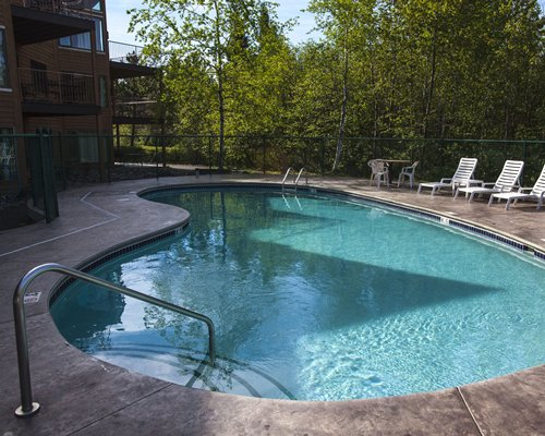 Outdoor swimming pool with chaise lounge chairs surrounded by wooded area.