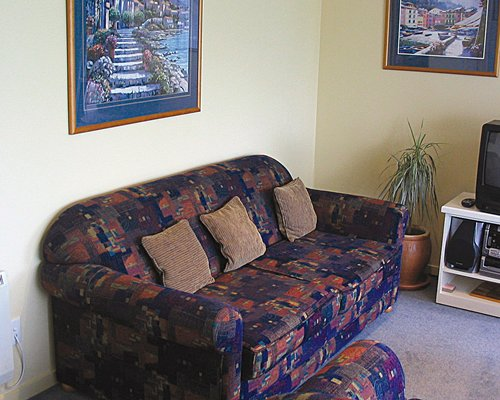 A well furnished living room with a television and sofa.