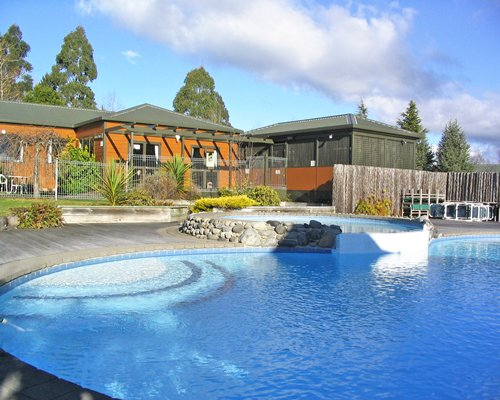 Exterior view of Kaimanawa Lodge with large outdoor swimming pool and landscaping.