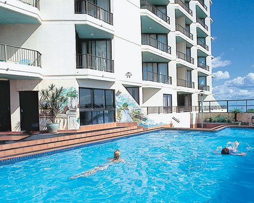 An outdoor swimming pool alongside the multi story resort unit.