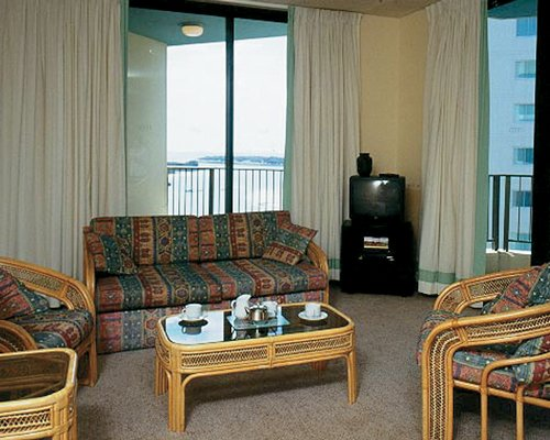 A well furnished living room with a double pull out sofa television and balcony.