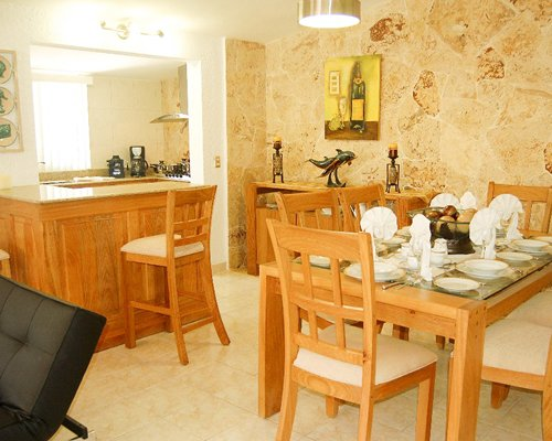 A well furnished dining area alongside the kitchen with a breakfast bar.