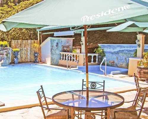 An outdoor swimming pool with hot tub sunshades and glass top dining table.