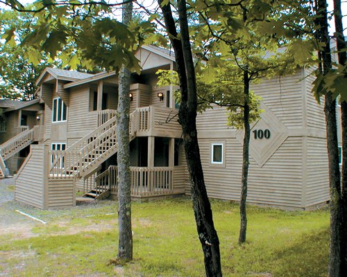 An exterior view of multi story resort units alongside trees.