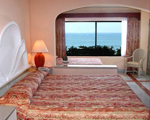 A well furnished bedroom with an ocean view.