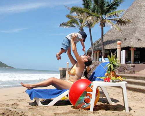 A woman playing with a kid in chaise lounge chair alongside the ocean.