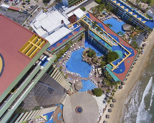 An aerial view of multi story resort units alongside the beach.