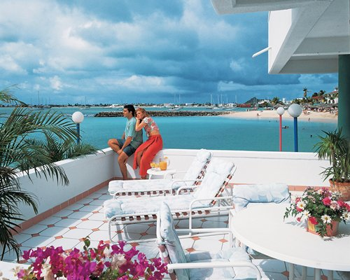 A couple in a balcony with chaise lounge chairs facing the ocean.